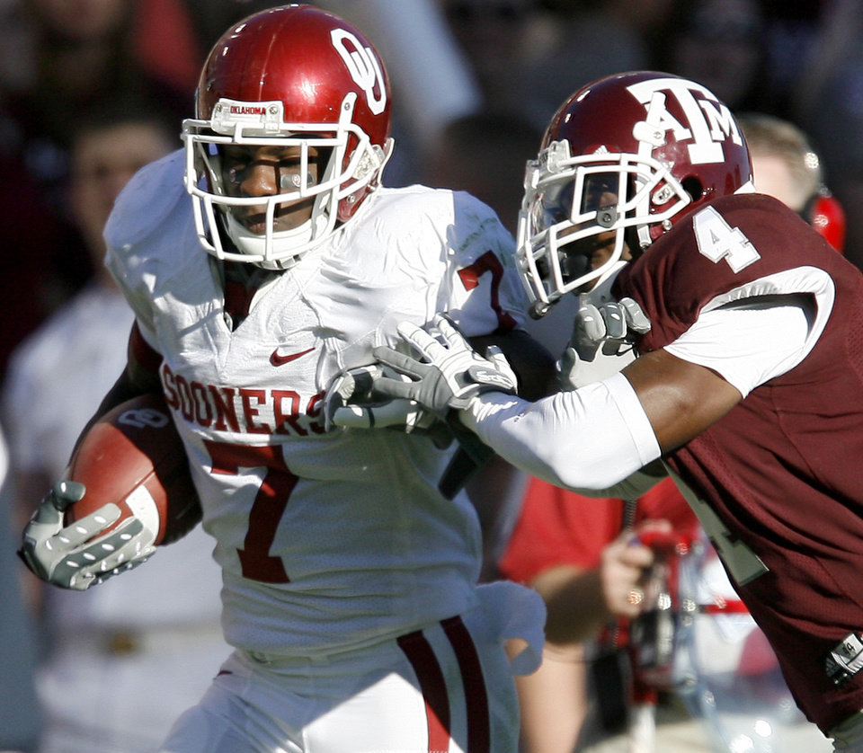 Photo - OU's DeMarco Murray fights off Danny Gorrer of Texas A&M during the college football game between the University of Oklahoma and Texas A&M University at Kyle Field in College Station, Texas, Saturday, November 8, 2008.  BY BRYAN TERRY, THE OKLAHOMAN