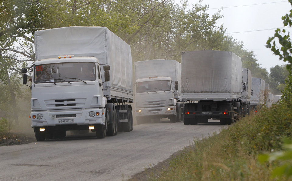 Photo - Russian aid trucks of the convoy roll on the main road to Luhansk near the town of Sukhodolsk, after it passed the border post at Izvaryne, eastern Ukraine, Friday, Aug. 22, 2014. The first trucks in a Russian aid convoy crossed into eastern Ukraine on Friday, after more than a week's delay. (AP Photo/Sergei Grits)