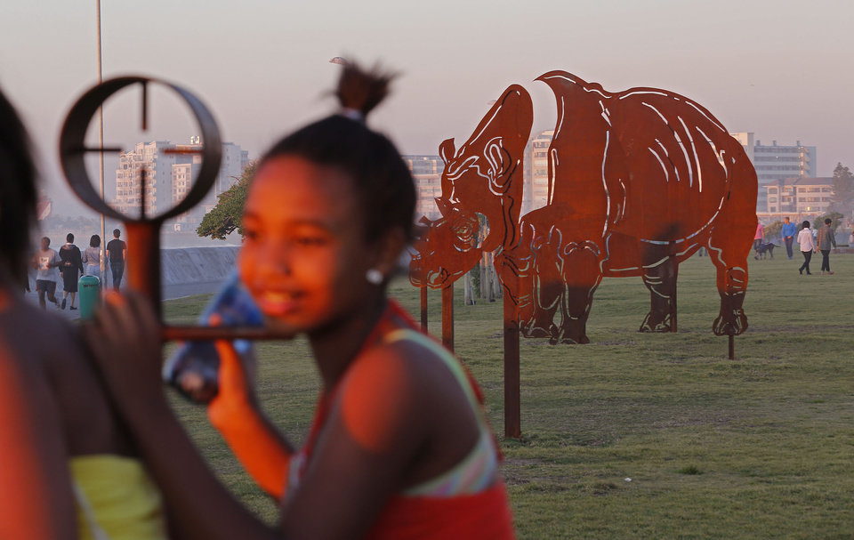 Photo - In this photo taken on Sunday, Aug. 24, 2014, a child stands next to an artistic piece on the promenade showing the crosshairs, left, of a rifle scope, with a Rhino body in the background in Cape Town, South Africa. It forms part of a public art display to emphasize the number of Rhinos being killed in South Africa by rhino poachers for the use of its horn in eastern medicine. The promenade offers a temporary art project, art54, with new pieces exhibited from time to time. (AP Photo/Schalk van Zuydam)