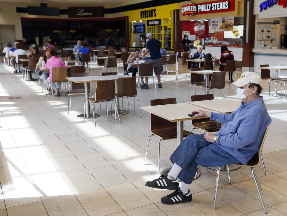 Photo - A man wears a mask as he sits in the food court at Penn Square Mall during the re-opening of the mall after being closed because of the coronavirus pandemic, in Oklahoma City, Friday, May 1, 2020. [Nate Billings/The Oklahoman]