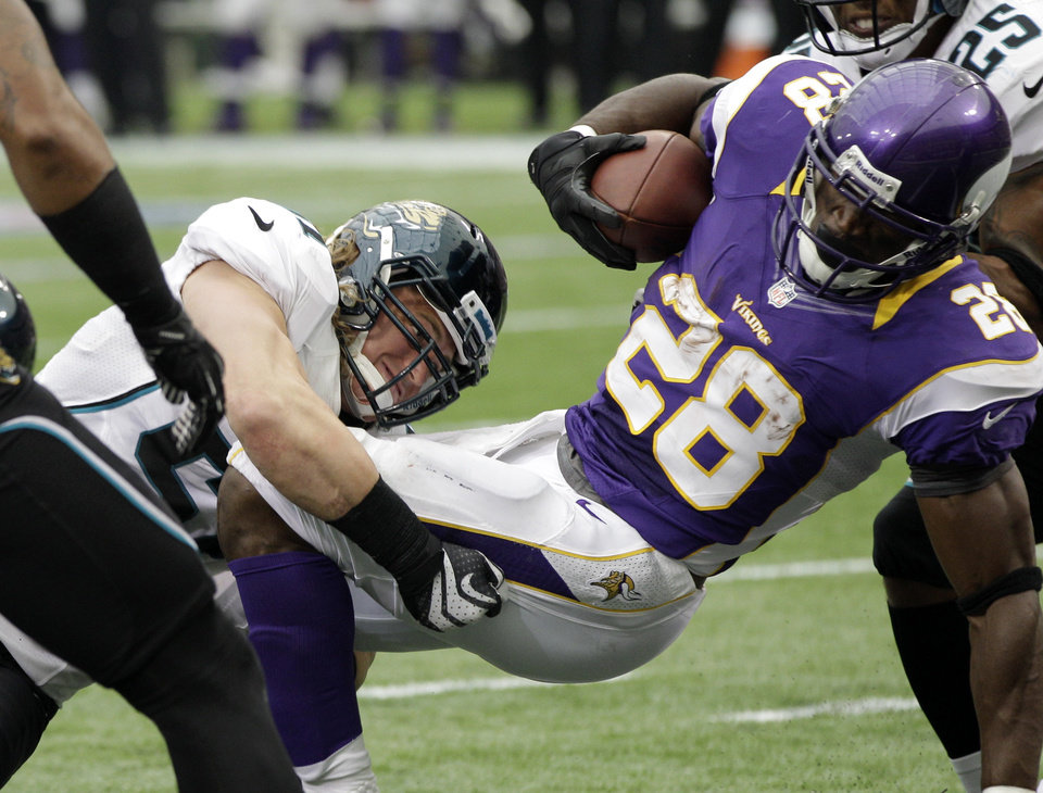 Photo -   Minnesota Vikings running back Adrian Peterson (28) scores a touchdown ahead of Jacksonville Jaguars linebacker Paul Posluszny, left, during the second half of an NFL football game on Sunday, Sept. 9, 2012, in Minneapolis. (AP Photo/Jim Mone)