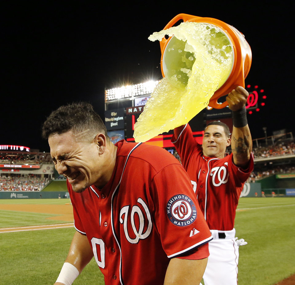 Photo - Washington Nationals' Wilson Ramos gets dunked by Ian Desmond after a baseball game against the Pittsburgh Pirates at Nationals Park, Saturday, Aug. 16, 2014, in Washington. Ramos hit the game-winner to score Bryce Harper. The Nationals won 4-3. (AP Photo/Alex Brandon)