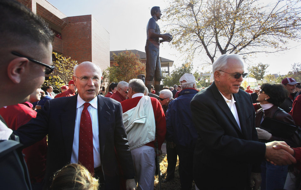 Photo - Jay Wilkinson, son of Bud Wilkinson (left) and former player Clendon Thomas (right) greet friends as Statues of 100 plus win head football coaches Benny Owen and Bud Wilkinson are unveiled before the college football game between the University of Oklahoma Sooners (OU) and the Texas Tech Red Raiders (TTU) across the street from the Gaylord Family Memorial Stadium on Saturday, Nov. 13, 2010, in Norman, Okla.  Photo by Steve Sisney, The Oklahoman