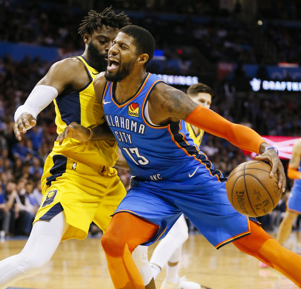 Photo - Oklahoma City's Paul George (13) tries to take the ball past Indiana's Tyreke Evans (12) during an NBA basketball game between the Indiana Pacers and the Oklahoma City Thunder at Chesapeake Energy Arena in Oklahoma City, Wednesday, March 27, 2019. Photo by Nate Billings, The Oklahoman