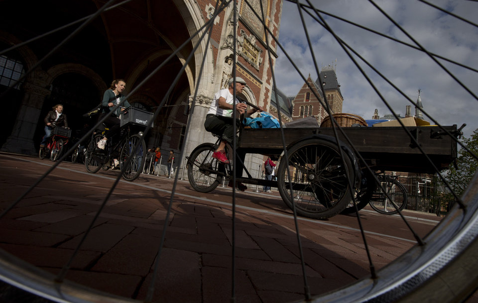 Photo - Bicycles pass through Rijksmuseum, in Amsterdam, Netherlands, Monday May 13, 2013, signaling the end of more than a decade of efforts by cyclists to ensure a passageway that runs under and through the Rijksmuseum would remain open to bike traffic. The museum, which houses masterpieces by Rembrandt van Rijn and Vincent van Gogh, among others, opened last month after a 10-year renovation. Architects and successive museum directors had opposed allowing bikes through, and a local government tried to have them barred on safety grounds. But in a city that has more bicycles than people, the bike lobby prevailed. (AP Photo/Peter Dejong)