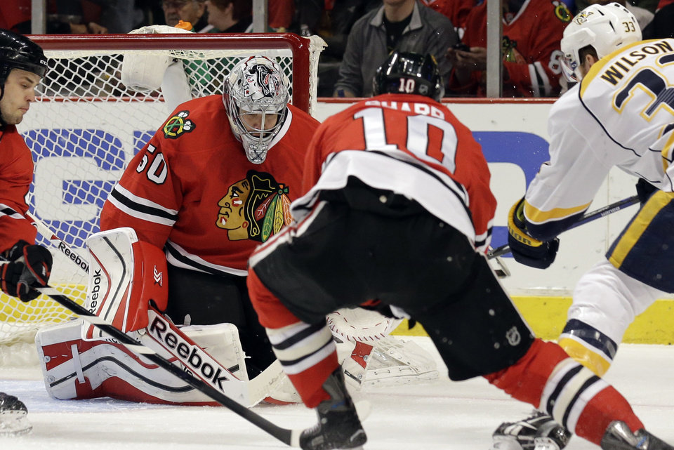 Photo - Chicago Blackhawks goalie Corey Crawford (50) saves the puck hit by Nashville Predators' Colin Wilson (33) during the first period of an NHL hockey game in Chicago, Friday, March 14, 2014. (AP Photo/Nam Y. Huh)