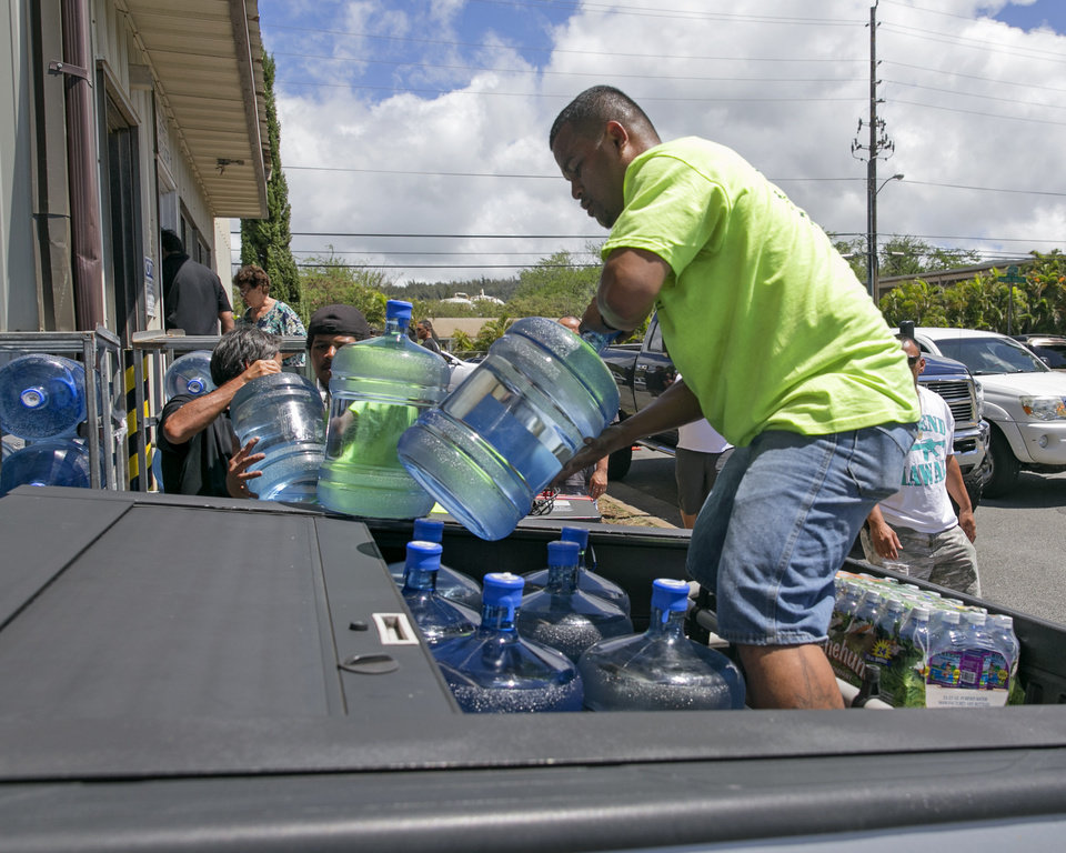 Photo - Workers at the Menehune Water Company load five gallon bottles of water into a customer's truck, Thursday, Aug. 7, 2014, in Aiea, Hawaii.  Hawaii is bracing for two back to back hurricanes, Iselle and Julio, which are on course to hit the Islands.  Bottles of water are quickly disappearing off shelves in Hawaii causing many people to line up for several hours to purchase water directly from the company.  (AP Photo/Marco Garcia)