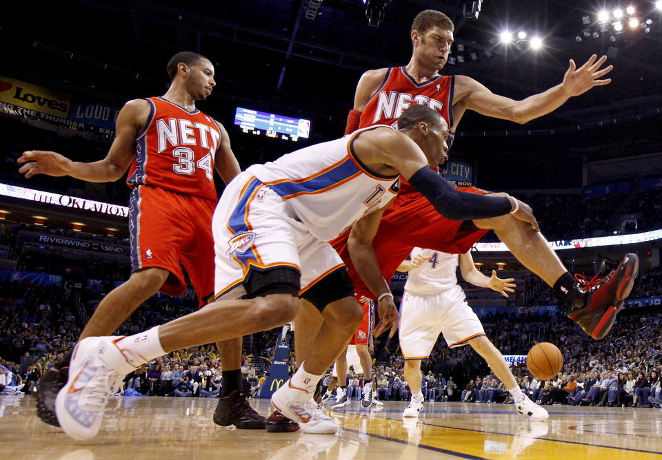 Photo - Oklahoma City's Russell Westbrook passes the ball around New Jersey's Devin Harris, left, and Brook Lopez during the NBA basketball game between the Oklahoma City Thunder and the New Jersey Nets at the Oklahoma City Arena, Wednesday, Dec. 29, 2010.  Photo by Bryan Terry, The Oklahoman ORG XMIT: KOD