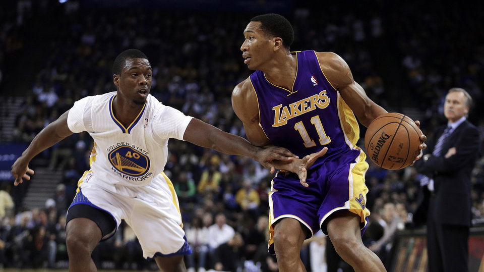 Photo - Los Angeles Lakers' Wesley Johnson, right, looks to pass away from Golden State Warriors' Harrison Barnes (40) during the first half of an NBA basketball game Saturday, Dec. 21, 2013, in Oakland, Calif. (AP Photo/Ben Margot)