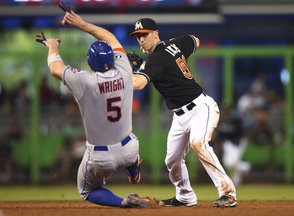 Photo - After forcing out New York Mets' David Wright (5) at second, Miami Marlins' Ed Lucas (59) makes the throw to first to complete a double play during the sixth inning of a baseball game in Miami, Saturday, June 21, 2014. Lucas Duda was out at first. The Mets won 4-0. (AP Photo/J Pat Carter)