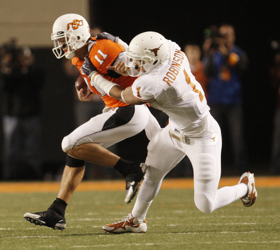 Photo - OSU quarteback Zac Robinson is collared by Keenan Robinson (1) during the college football game between the Oklahoma State University Cowboys (OSU) and the University of Texas Longhorns (UT) at Boone Pickens Stadium in Stillwater, Okla., Saturday, Oct. 31, 2009. Photo by Doug Hoke, The Oklahoman