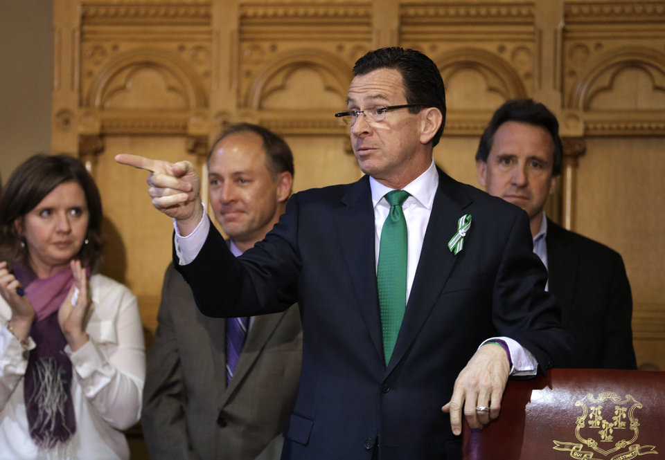 Photo - Connecticut Gov. Dannel P. Malloy, second from right, gestures at the conclusion of a legislation signing ceremony as Jackie and Mark Barden, left and second from left respectively, parents of Sandy Hook shooting victim Daniel Barden, and Neil Heslin, right, father of Sandy Hook shooting victim Jesse Lewis, right, look on at the Capitol in Hartford, Conn., Thursday, April 4, 2013. The legislation signed by Malloy adds more than 100 firearms to the state's assault weapons ban, sets eligibility rules for buying ammunition, and creates what officials have called the nation's first dangerous weapon offender registry. (AP Photo/Steven Senne)