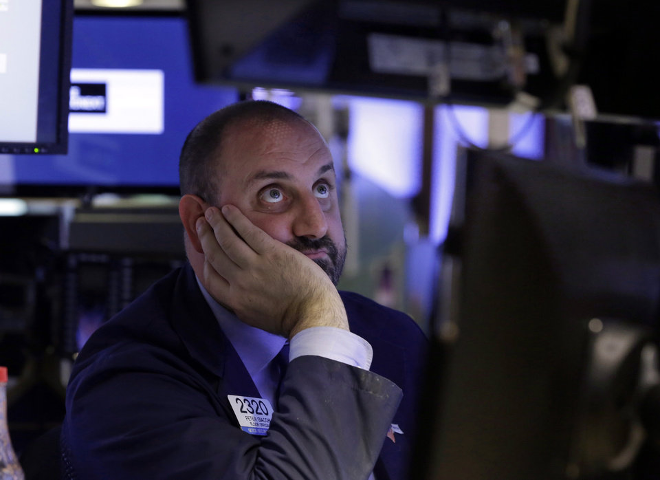 Photo - Specialist Peter Giacchi watches his screens as he works on the floor of the New York Stock Exchange, Monday, June 24, 2013. Traders in the U.S. dumped stocks, bonds and commodities, prompted by signs of distress in China's economy and worries about the end of the Federal Reserve bank's easy money policies. (AP Photo/Richard Drew)