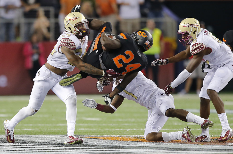 Photo - Florida State's Terrance Smith (24), Tyler Hunter (1) and Jalen Ramsey (8) upend Oklahoma State's Tyreek Hill (24) during the college football game between Oklahoma State University (OSU) and Florida State University (FSU) at the AdvoCare Cowboys Classic at AT&T Stadium in Arlington, Texas on Saturday, Aug. 30, 2014. Photo by Chris Landsberger, The Oklahoman