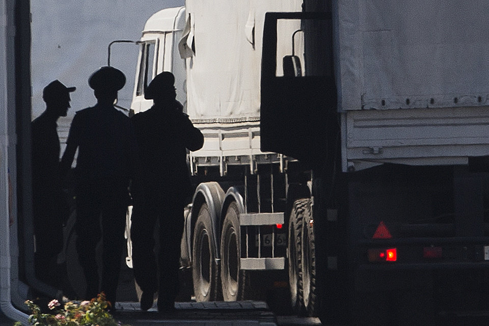 Photo - A driver, left, and Russian custom service officers stand near trucks of the Russian aid convoy which are searched at a Russian inspection zone inside a border control point with Ukraine in the Russian town of Donetsk, Rostov-on-Don region, Russia, Friday, Aug. 22, 2014. The first trucks of the Russian aid convoy crossed the Ukrainian inspection zone Friday morning. (AP Photo/Pavel Golovkin)