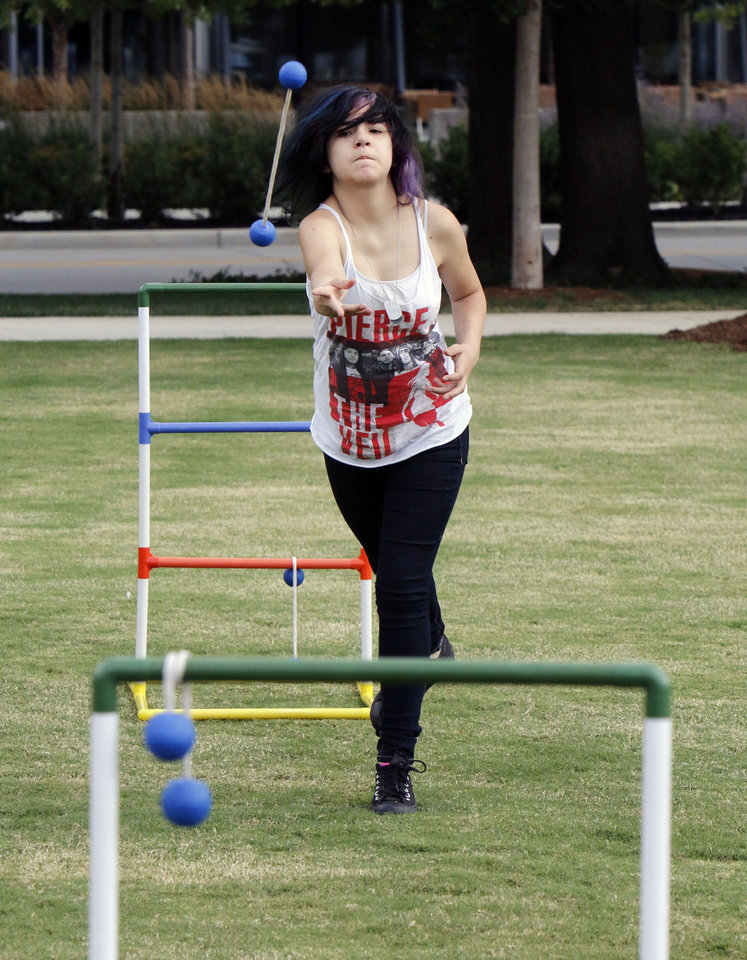 Photo -  Indigo Martinez plays a game of ladder ball during Games on the Great Lawn at the Myriad Gardens in downtown Oklahoma City. Photo by Paul Hellstern, The Oklahoman   PAUL HELLSTERN -