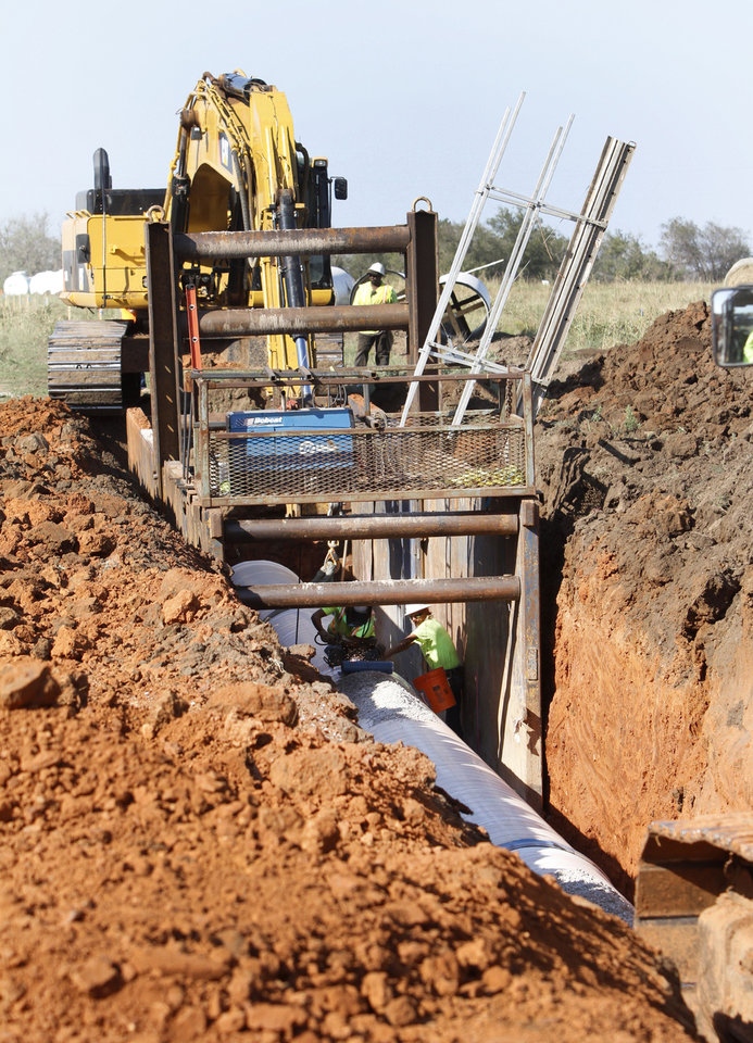 Workers lay pipe in a utility project that will ready the area on the east side of Will Rogers World Airport for redevelopment. Photo by Steve Gooch, The Oklahoman