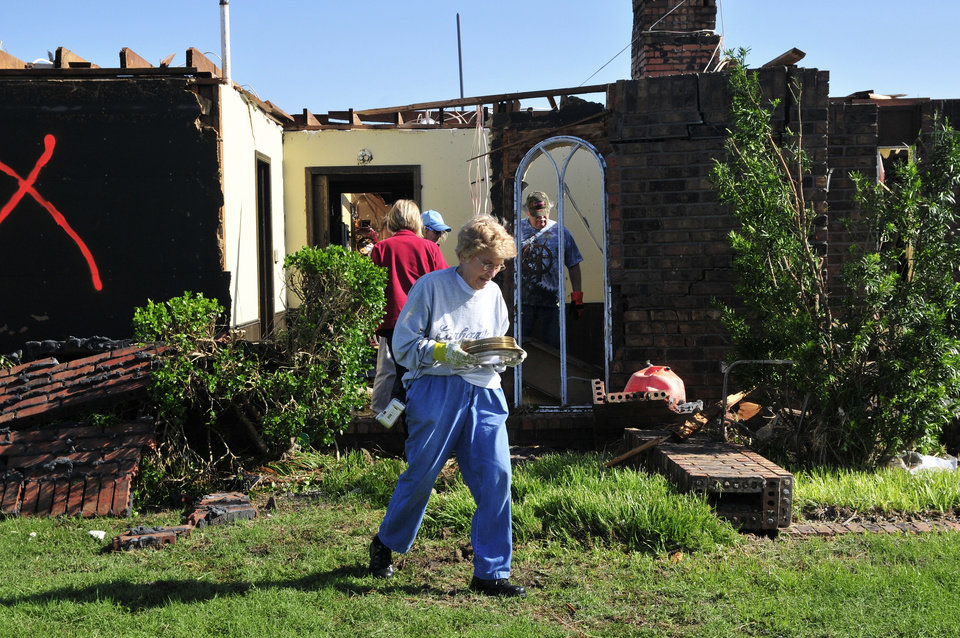 Photo - Rilma Hulett carries a dish set from her friend Bobbie Steenbergen's home that was destroyed by the tornado that swept through Central Oklahoma Friday afternoon on Saturday June 1, 2013 in El Reno Okla. Emergency officials set out Saturday morning to see how much damage a violent burst of thunderstorms and tornadoes caused as it swept across the Midwest overnight.  (AP Photo/Nick Oxford)