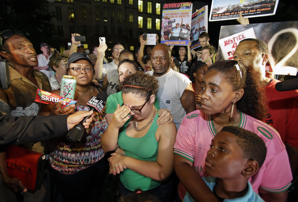 Photo - Demonstrators outside the Seminole County Courthouse react after hearing the verdict of not guilty in the trial of George Zimmerman, Saturday, July 13, 2013, in Sanford, Fla. Zimmerman had been charged with the 2012 shooting death of Trayvon Martin. (AP Photo/John Raoux) ORG XMIT: FLJR113