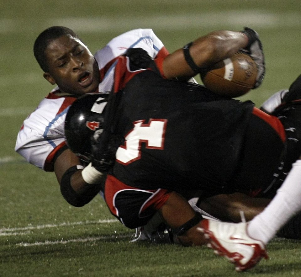 Despite losing his helmet, Dallas (Skyline) linebacker, and OU signee, Corey Nelson pulls down Carrollton (Tex.) Creekview tailback Ryan Wilson during a game in 2008. PHOTO COURTESY DALLAS MORNING NEWS