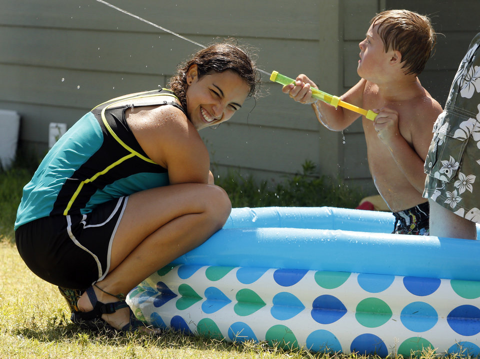 Photo -  Volunteer Taylor Cannon dodges a water cannon being sprayed by camper Reis Wathen, 11, at Camp ClapHans, an outreach program of the J.D. McCarty Center in Norman. PHOTO BY STEVE SISNEY, THE OKLAHOMAN   STEVE SISNEY -
