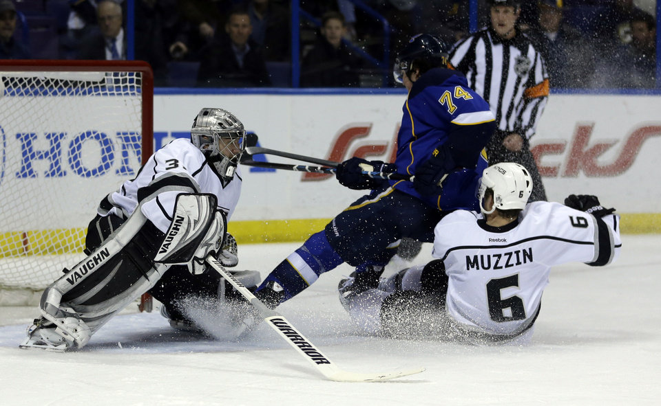 Photo - St. Louis Blues' T.J. Oshie (74) is taken down from behind by Los Angeles Kings' Jake Muzzin (6) as Kings goalie Jonathan Quick watches during the second period of an NHL hockey game, Thursday, Jan. 16, 2014, in St. Louis. Oshie was awarded a penalty shot and scored following the play. (AP Photo/Jeff Roberson)