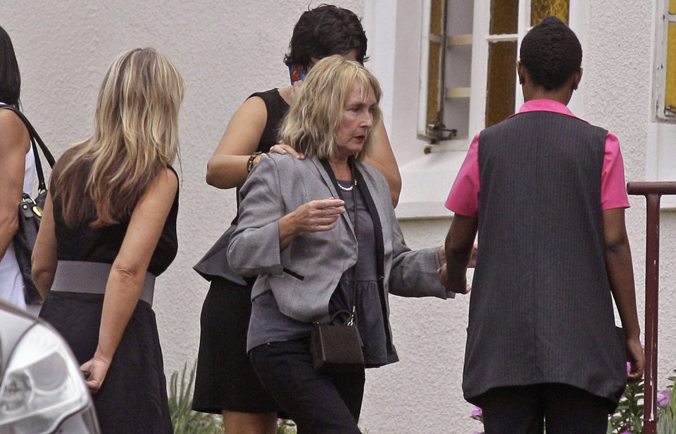 Photo - June Steenkamp, center, the mother of Reeva Steenkamp, arrives for her funeral in Port Elizabeth, South Africa, Tuesday, Feb. 19, 2013. Olympic athlete Oscar Pistorius is charged with the premeditated murder of Reeva Steenkamp on Valentine's Day. The defense lawyer says it was an accidental shooting. (AP Photo/Schalk van Zuydam)