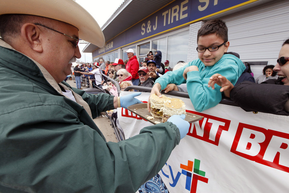 Canadian County Sheriff Randall Edwards passes out burgers during the Burger Day Festival in El Reno. PAUL HELLSTERN - Oklahoman