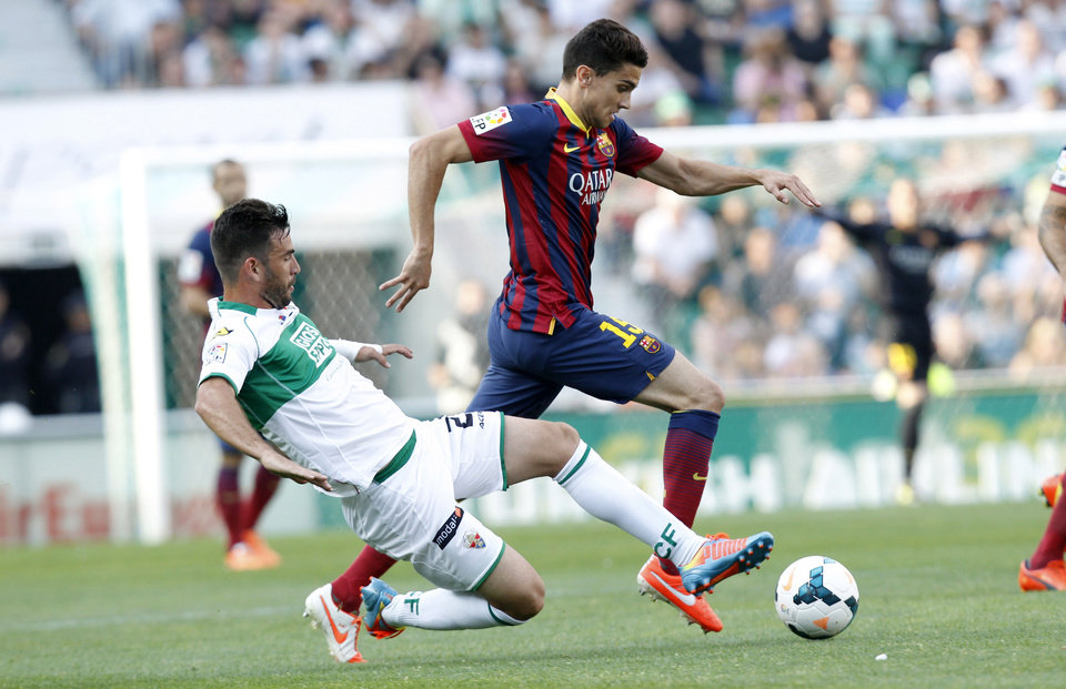 Photo - Barcelona's Marc Bartra duels for the ball with Elche's Domingo Cisma Gonzalez during a Spanish La Liga soccer match at the Martinez Valero stadium in Elche, Spain, on Sunday, May 11, 2014. (AP Photo/Alberto Saiz)