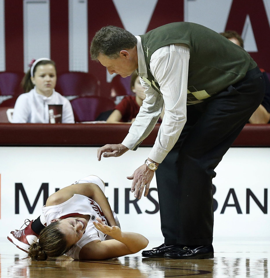 Photo - North Texas head coach Mike Petersen is the first to reach Oklahoma's Whitney Hand  after she falls to the floor following an injury as the University of Oklahoma Sooners (OU) play the North Texas Mean Green in NCAA, women's college basketball at The Lloyd Noble Center on Thursday, Dec. 6, 2012  in Norman, Okla. Photo by Steve Sisney, The Oklahoman
