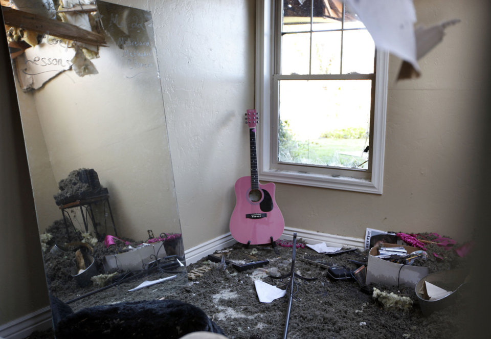 A mirror and guitar sit unharmed in a house damaged by a tornado, Sunday, April, 15, 2012. A tornado struck Woodward early Sunday morning. Photo by Sarah Phipps, The Oklahoman.