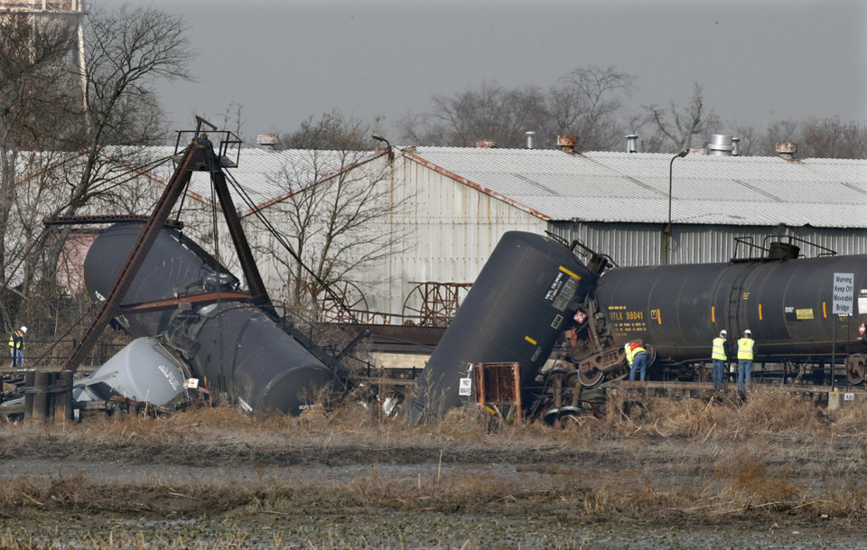 Photo - Officials work the scene of derailed freight train tank cars in Paulsboro, N.J., Friday, Nov. 30, 2012. People in three southern New Jersey towns were told Friday to stay inside after a freight train derailed and several tanker cars carrying hazardous materials toppled from a bridge and into a creek. At least one tanker car may contain vinyl chloride, Gloucester County Emergency Management director J. Thomas Butts told WPVI-TV. (AP Photo/Mel Evans)