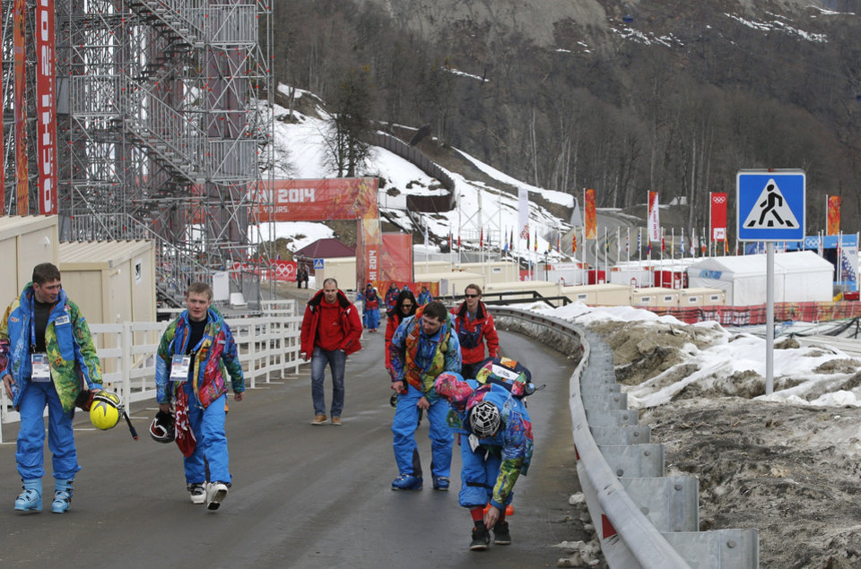 Photo - Course workers walk on the road behind the finish area of the alpine ski venue at the Sochi 2014 Winter Olympics, Tuesday, Feb. 11, 2014, in Krasnaya Polyana, Russia. Warm temperatures in the mountains was a factor in the cancellation of Women's downhill training on Tuesday. (AP Photo/Christophe Ena)