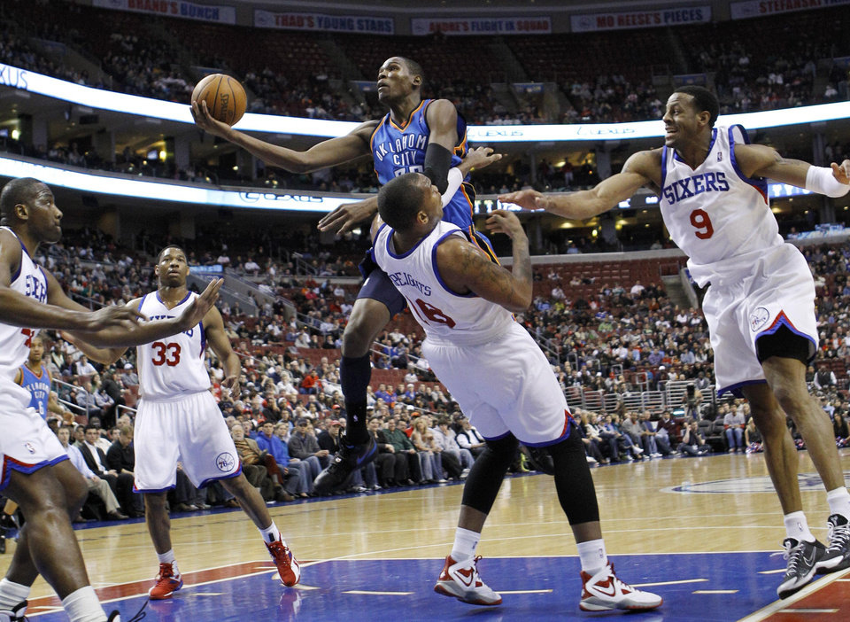 Photo - Oklahoma City's Kevin Durant, center, goes up for a shot as Philadelphia 76ers' Elton Brand, from left, Willie Green, Marreese Speights and Andre Iguodala try to defend. AP PHOTO
