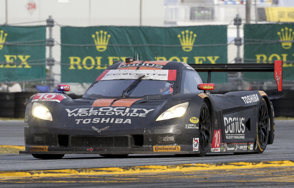 Photo - Ricky Taylor drives the Wayne Taylor Racing Corvette DP through the east horseshoe turn during the IMSA Series Rolex 24 hour auto race at Daytona International Speedway in Daytona Beach, Fla., Sunday, Jan. 26, 2014.(AP Photo/David Graham)