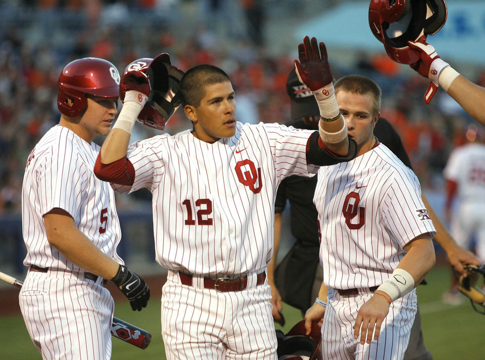 Photo - Oklahoma's Hector Lorenzana, center, is greeted by teammates including Colt Bickerstaff, left, and Hunter Haley, right, after scoring against Oklahoma State during a college baseball game Friday, May 10, 2013, in Tulsa, Okla. (AP Photo/Tulsa World, Matt Barnard) ORG XMIT: OKTUL306