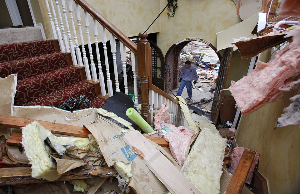 Photo - Residents work to clean up damage to a home in the Oaktree addition on Wednesday, Feb. 11, 2009, after a tornado hit the area on Tuesday in Edmond, Okla. PHOTO BY CHRIS LANDSBERGER, THE OKLAHOMAN