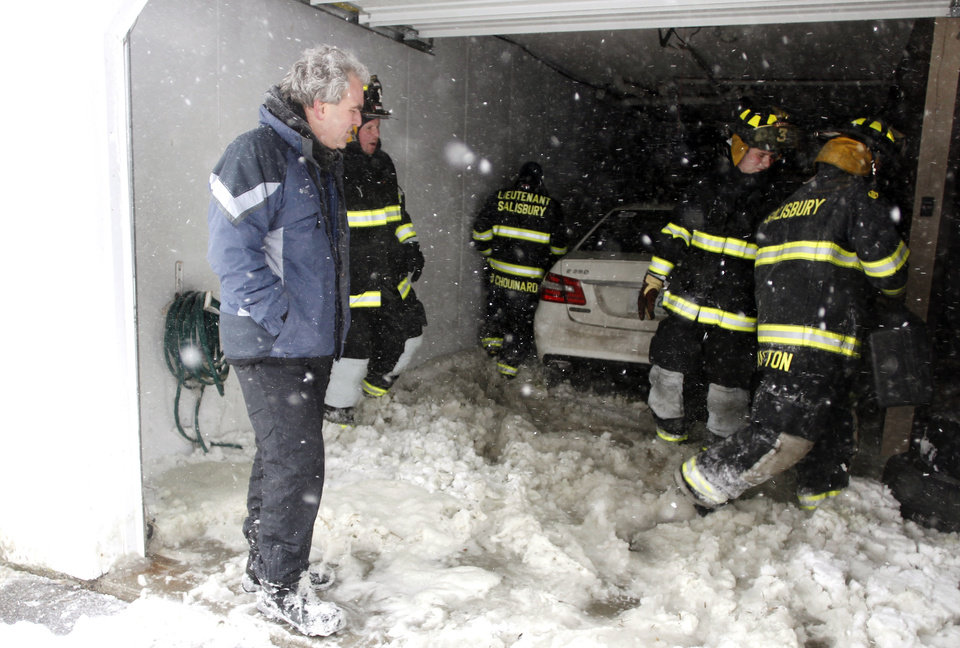 Homeowner Paul Descateaux, left, stands by as firefighters enter his home after Descateaux smelled smoke after his home was flooded by the ocean, Saturday, Feb. 9, 2013, in Salisbury, Mass. (AP Photo/Winslow Townson)