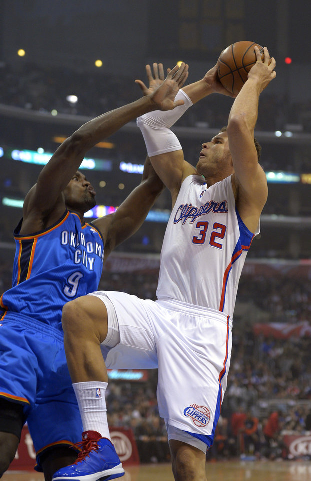 Photo - Los Angeles Clippers forward Blake Griffin, right, puts up a shot as tforward Serge Ibaka, of Congo, defends during the first half of their NBA basketball game, Tuesday, Jan. 22, 2013, in Los Angeles.  (AP Photo/Mark J. Terrill)