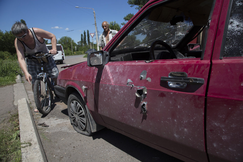 Photo - People examine a damaged car after shelling near a gas station in the city of Kramatorsk, Donetsk region, eastern Ukraine, Thursday, July 3, 2014. The driver of this car was killed. Residential areas came under shelling on and Thursday from government forces. (AP Photo/Dmitry Lovetsky)