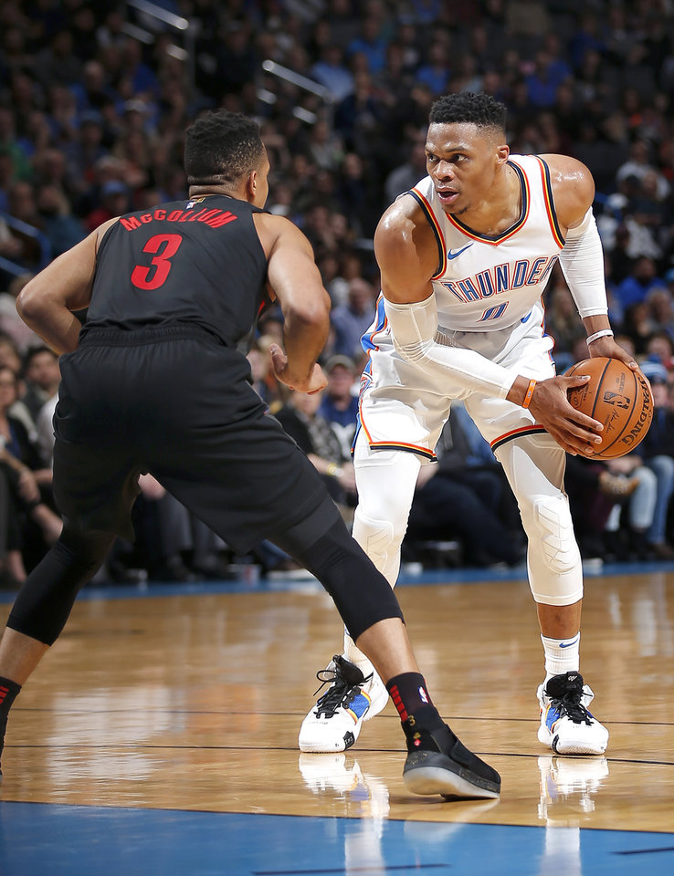 Photo - Oklahoma City's Russell Westbrook (0) looks to get by Portland's CJ McCollum (3) during the NBA basketball game between the Oklahoma City Thunder and the Portland Trail Blazers at Chesapeake Energy Arena in Oklahoma City, Tuesday, Jan. 22, 2019. Photo by Sarah Phipps, The Oklahoman