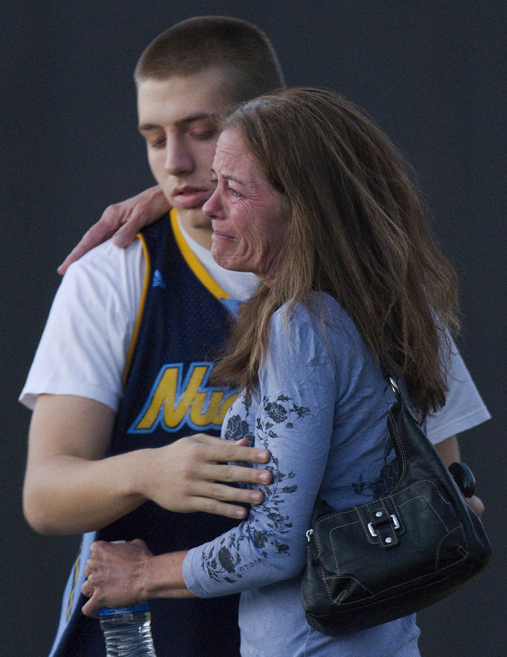 Photo - Jacob Stevens, 18, hugs his mother Tammi Stevens after being interview by police outside Gateway High School where witness were brought for questioning after a shooting at a movie theater, Friday, July 20, 2012 in Denver. A gunman wearing a gas mask set off an unknown gas and fired into a crowded movie theater at a midnight opening of the Batman movie