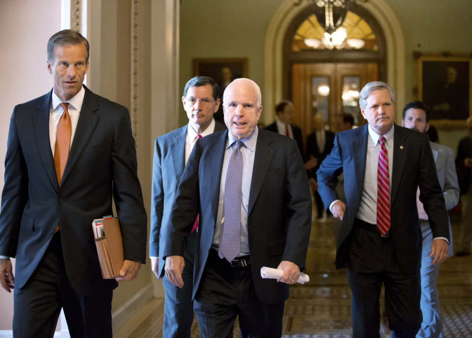 Photo - Republican senators, from left, Sen. John Thune, R-S.D., Sen. John Barrasso, R-Wyo., Sen. John McCain, R-Ariz., and Sen. John Hoeven, R-N.D., walk from the floor to a closed-door caucus after a compromise between the Democratic majority and the GOP minority on filibuster rules, at the Capitol in Washington, Tuesday, July 16, 2013. Senate Majority Leader Harry Reid credited Sen. McCain, with helping broker a breakthrough.The Senate just voted 71-29 to end a two-year Republican blockade that was preventing Richard Cordray from winning confirmation as director of the Consumer Financial Protection Bureau.  (AP Photo/J. Scott Applewhite)
