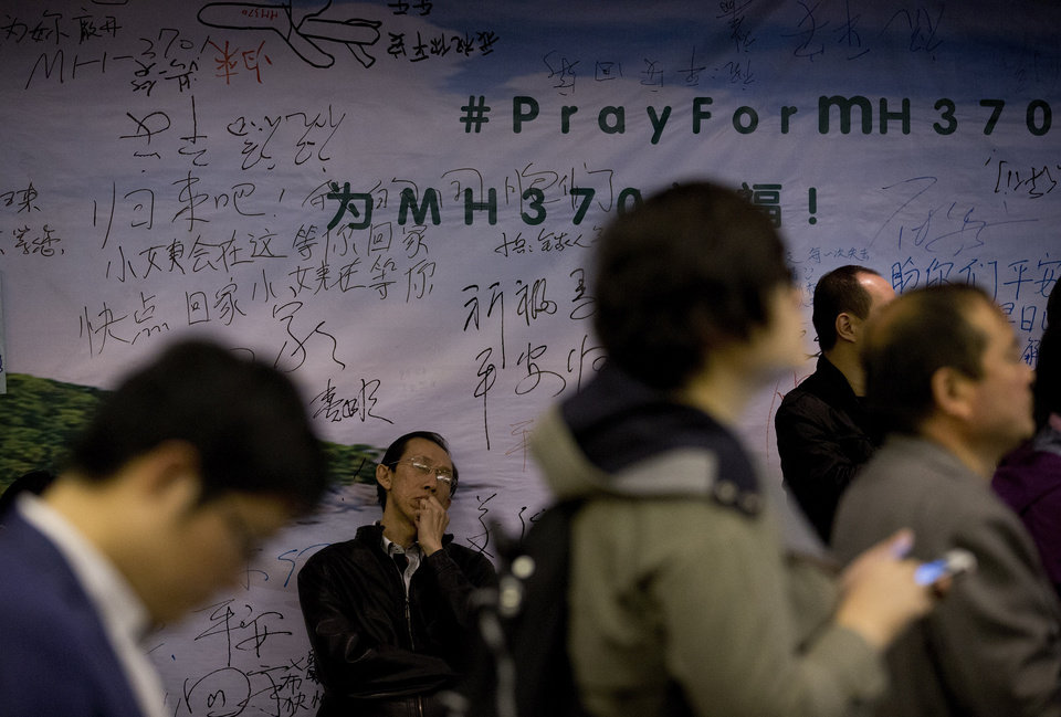 Photo - A man, center, one of the relatives of Chinese passengers aboard the missing Malaysia Airlines flight MH370 takes a nap against the wall displaying messages of wishes for the passengers during a briefing held by Malaysia officials at a hotel in Beijing, China Friday, April 11, 2014. Authorities are confident that signals detected deep in the Indian Ocean are from the missing Malaysian jet's black boxes, Australia's Prime Minister  Tony Abbott said Friday, raising hopes they are near solving one of aviation's most perplexing mysteries. (AP Photo/Andy Wong)