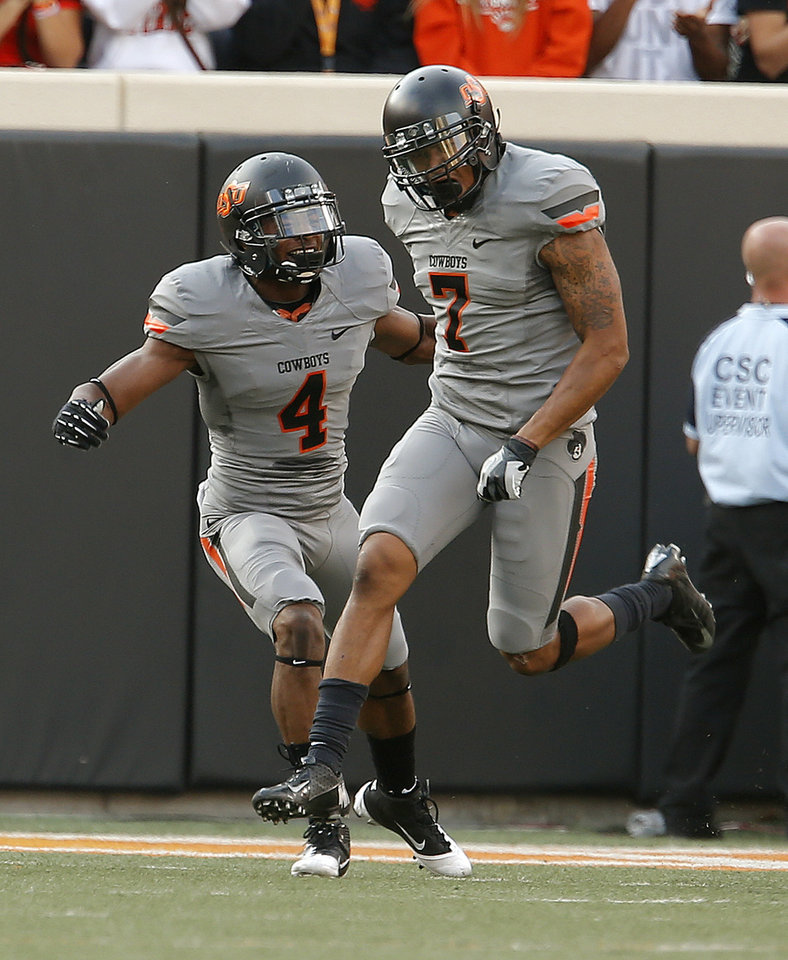 Photo - Oklahoma State's Justin Gilbert (4) and Shamiel Gary (7) celebrate a play during a college football game between Oklahoma State University (OSU) and the West Virginia University at Boone Pickens Stadium in Stillwater, Okla., Saturday, Nov. 10, 2012. OSU won 55-34. Photo by Sarah Phipps, The Oklahoman