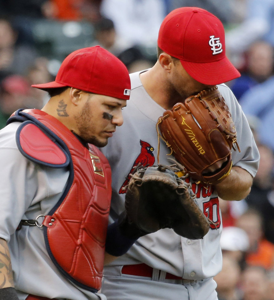 Photo - St. Louis Cardinals catcher Yadier Molina, left, listens to starting pitcher Adam Wainwright during the second inning of a baseball game against the Chicago Cubs Friday, May 2, 2014, in Chicago. (AP Photo/Charles Rex Arbogast)