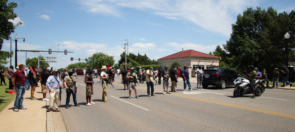 Photo - Marchers block traffic on NE 23rd  in front of the Governor's Mansion at a 1,000 brothers and sisters in arms for second amendment walk by predominantly black men and women to advocate for their second amendment rights, Saturday, June 20, 2020. [Doug Hoke/The Oklahoman]