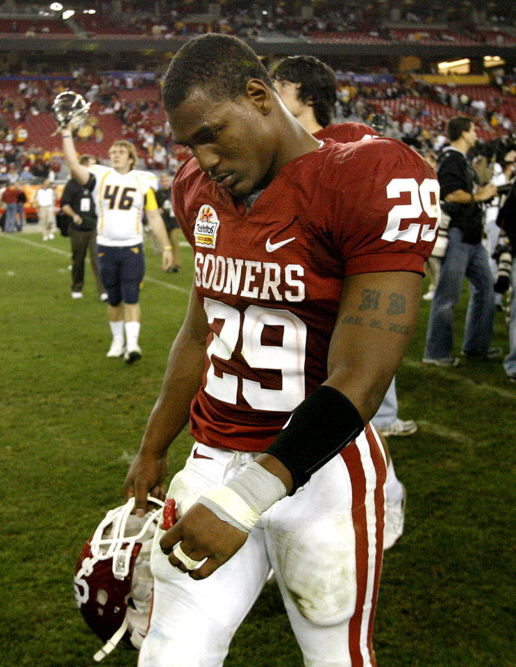Photo - OU's Chris Brown walks off the field after the Fiesta Bowl college football game between the University of Oklahoma Sooners (OU) and the West Virginia University Mountaineers (WVU) at The University of Phoenix Stadium on Wednesday, Jan. 2, 2008, in Glendale, Ariz. 