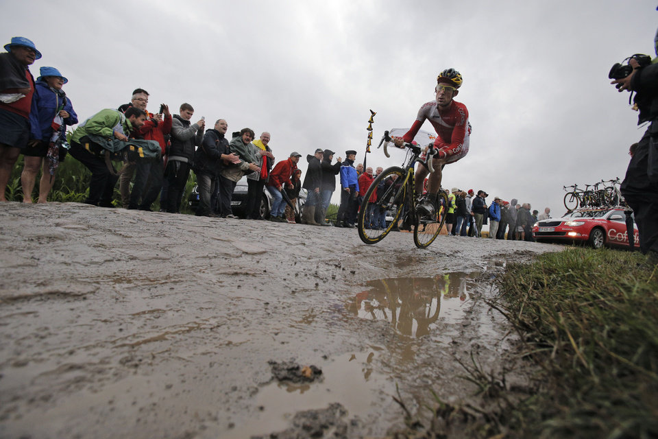 Photo - A rider passes over a cobblestone sector during the fifth stage of the Tour de France cycling race over 155 kilometers (96.3 miles) with start in Ypres, Belgium, and finish in Arenberg, France, Wednesday, July 9, 2014. (AP Photo/Christophe Ena)