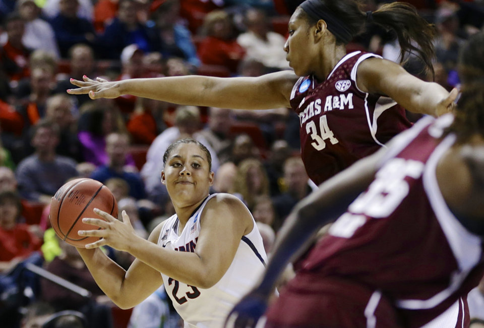 Photo - Connecticut's Kaleena Mosqueda-Lewis (23) looks to pass the ball against the defense of Texas A&M's Karla Gilbert (34) during the first half of a regional final game in the NCAA college basketball tournament in Lincoln, Neb., Monday, March 31, 2014. (AP Photo/Nati Harnik)